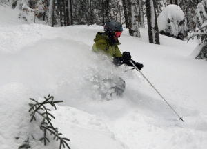 An image of Erica spraying powder as she skis in fresh snow from Winter Storm Harper at Bolton Valley Resort in Vermont