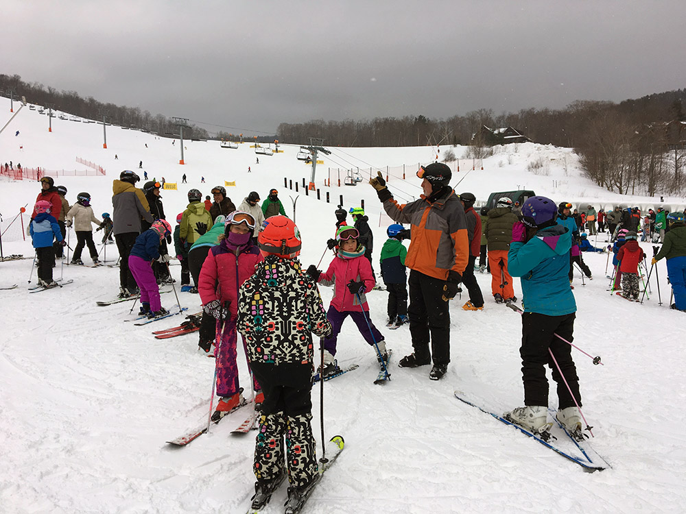 An image of participants grouping up for our weekly BJAMS ski program at the base of Spruce Peak at Stowe Mountain Resort in Vermont
