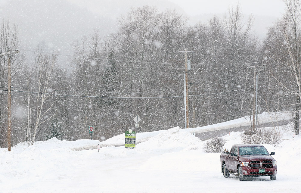 An image of big flakes of snwo falling at the Timberline base area at Bolton Valley Resort in Vermont