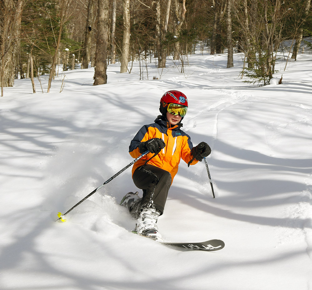 An image of Dylan Telemark skiing in powder at Bolton Valley Resort in Vermont.