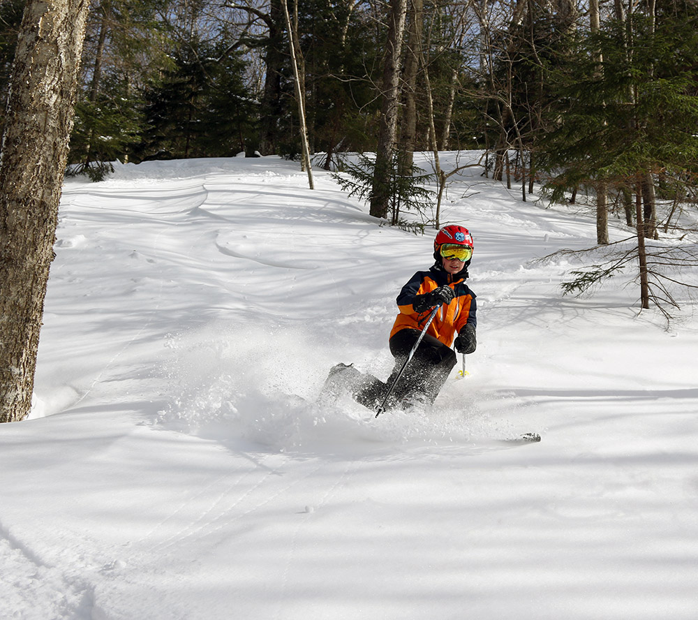 An image of Dylan Telemark skiing in powder on Maria's at Bolton Valley Resort in Vermont
