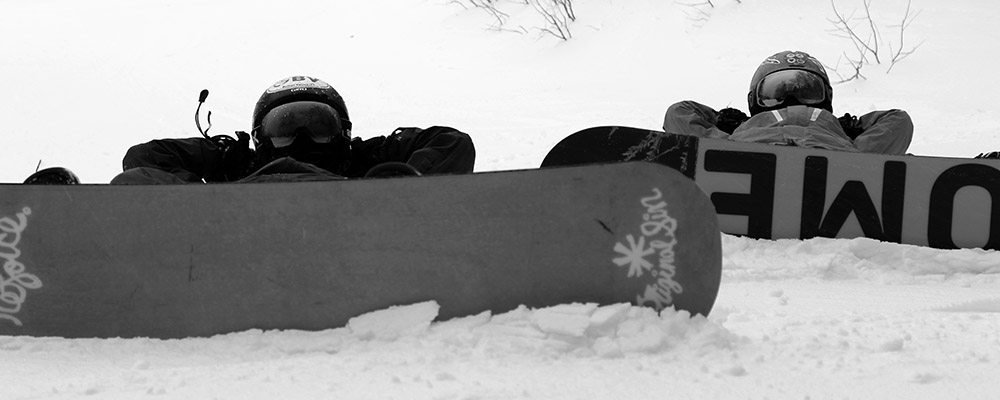 Ty and Dylan lying down on the snow with their snowboards on at Stowe Mountain Resort in Vermont