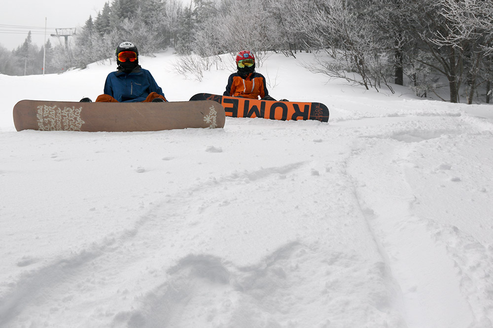 An image of Ty and Dylan on snowboards along the edge of the Switchback trail at Stowe Mountain Resort in Vermont