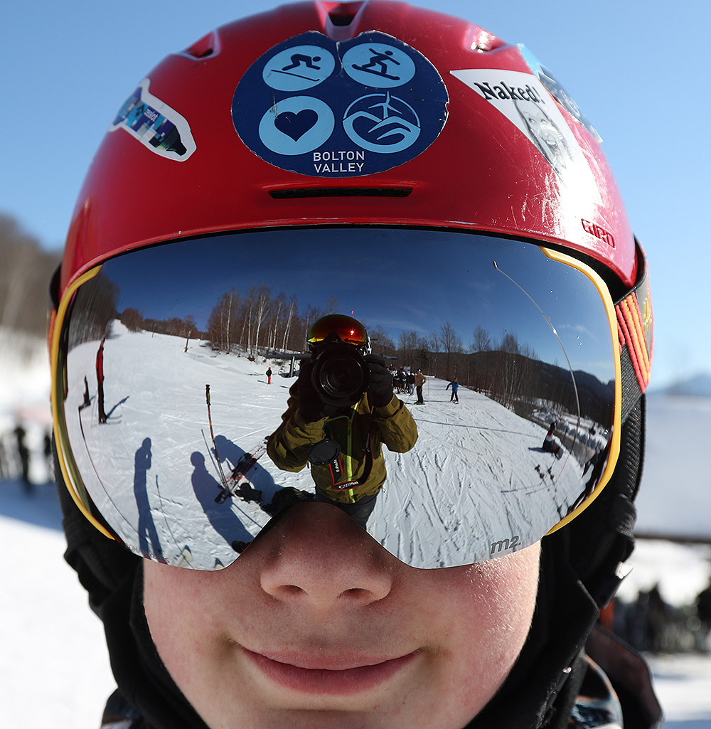 An image of Dylan wearing a silver ski goggle lens on a sunny day at the Timberline Base of Bolton Valley Ski Resort in Vermont
