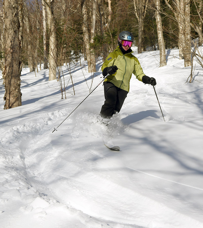 An image of Erica skiing powder in the Snow Hole area at Bolton Valley Resort in Vermont