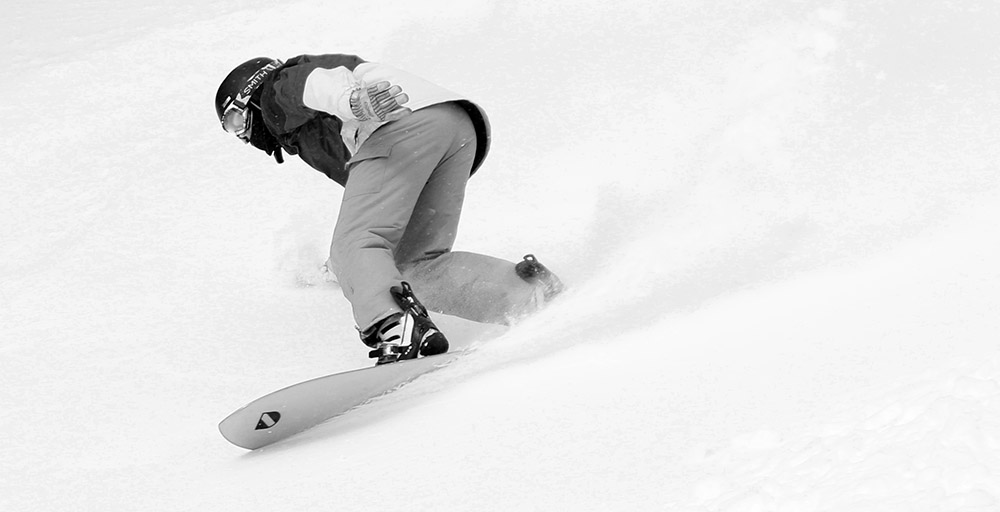 An image of a snowboarder riding in powder snow near the sumit of Spruce Peak at Stowe Mountain Resort in Vermont