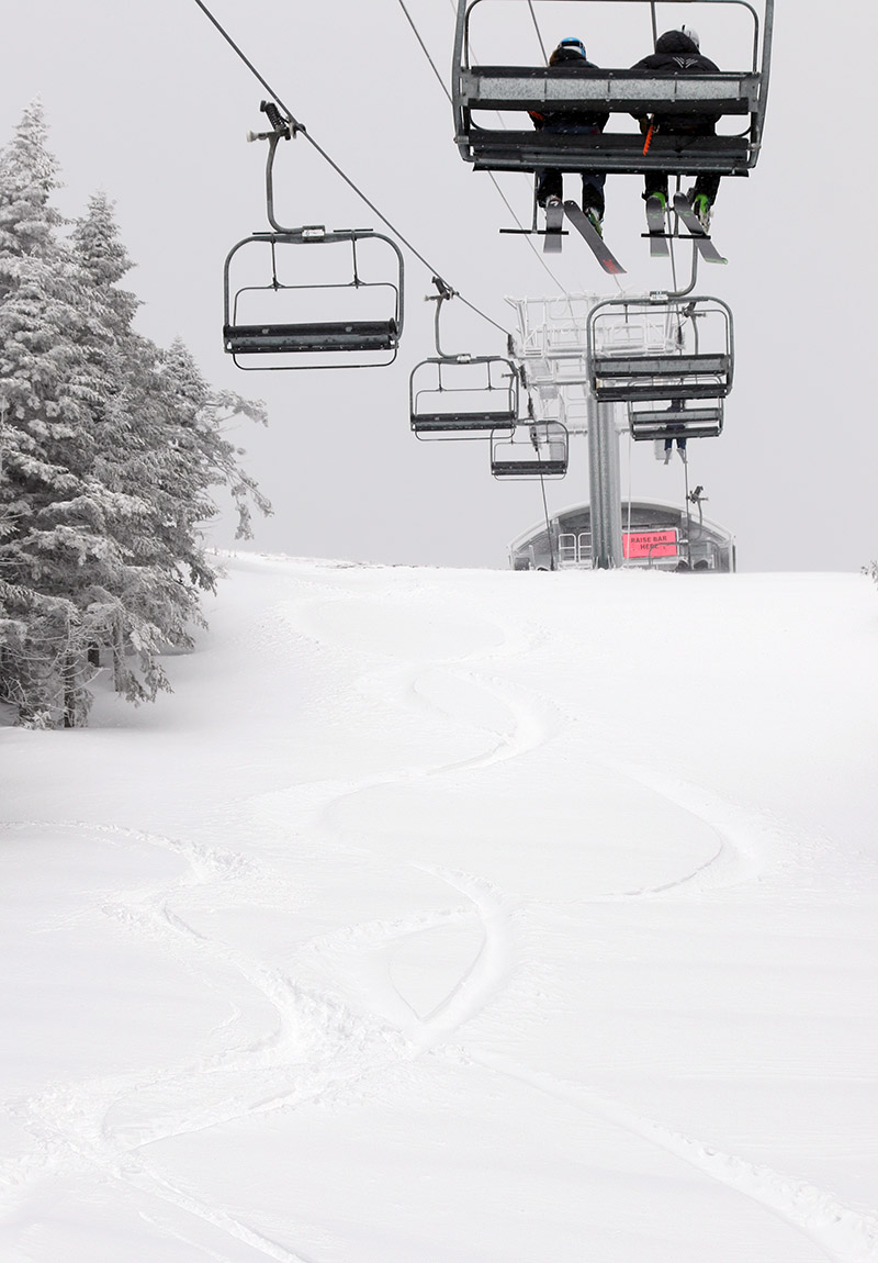 An image of ski tracks in powder below the Sensation Quad Chairlift at Stowe Mountain Resort during Winter Storm Taylor