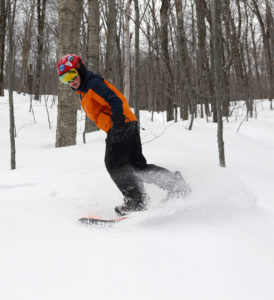An image of Dylan snowboardinig in powder from the back side of Winter Storm Ulmer in the Toll House Trees at Stowe Mountain Resort in Vermont