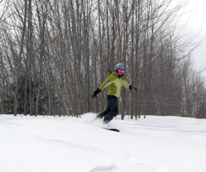 An image of Erica snowboarding in powder in the Toll House area at Stowe Mountain Resort in Vermont