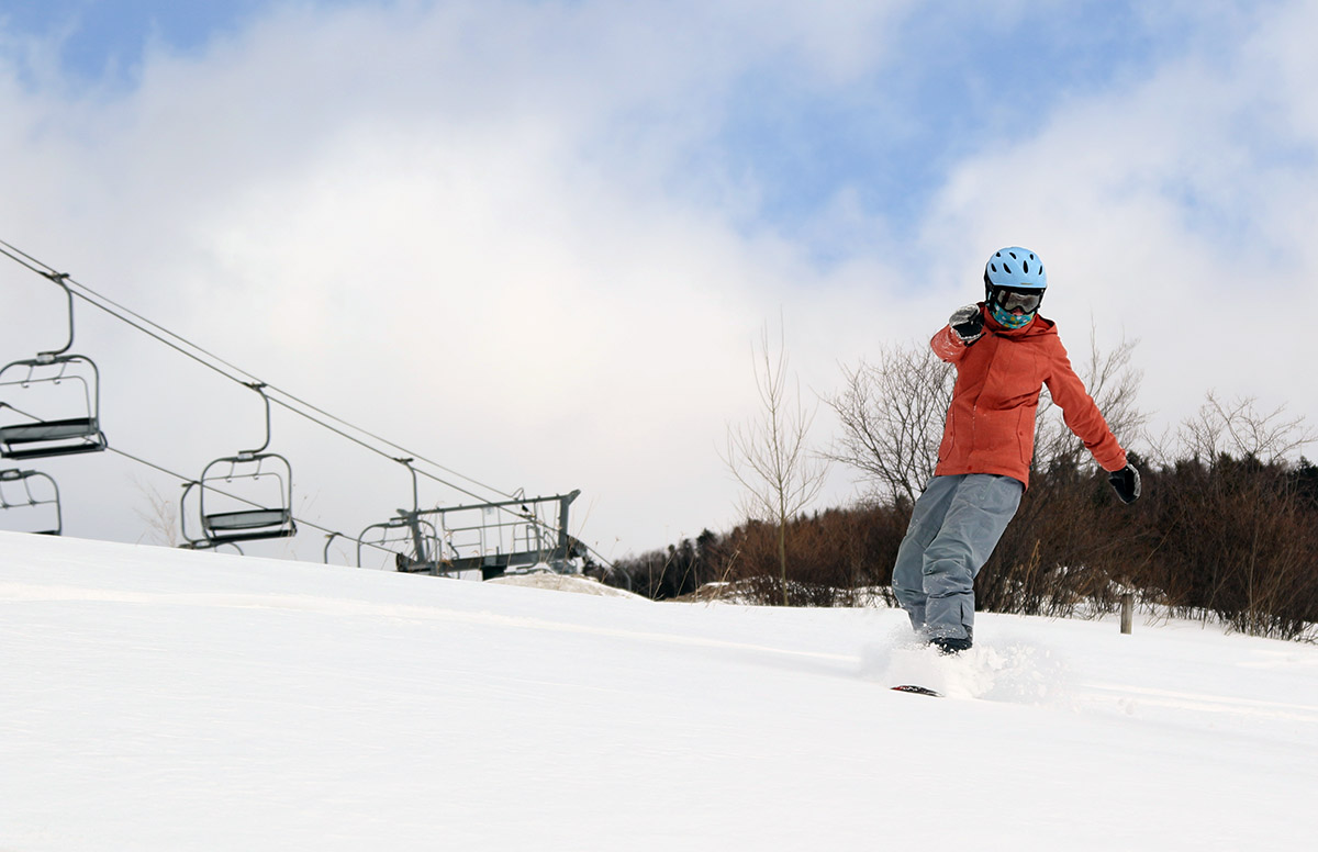 An image of Molly riding her snowboard in the Inspiration/Adventure Triple Chair area at Stowe Mountian Resort in Vermont after some back side snow from Winter Storm Ulmer