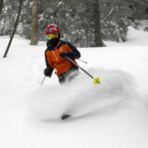 An image of Dylan skiing in powder at Bolton Valley Ski Resort in Vermont