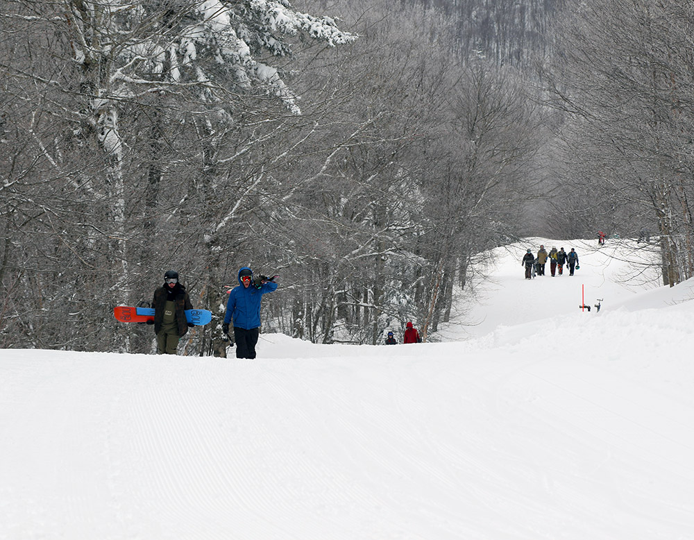 An image of skiers and snowboarders hiking up the Villager trail at Bolton Valley in Vermont