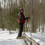 An image of Brian showing the four to five foot snowpack that is level with the railings of a bridge along the Ranch Brook in the Mt. Mansfield sidecountry near Stowe Mountain Resort in Vermont