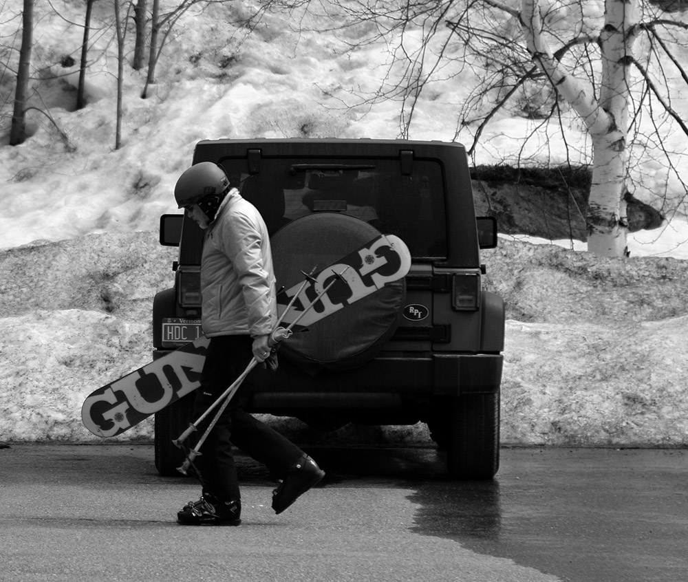 An image of a man with a monoski walking through the Timberline parking lot at Bolton Valley Resort in Vermont