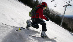 An image of Dylan Telemark skiing in spring snow on the Spillway trail at Bolton Valley Resort in Vermont