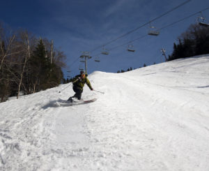An image of Jay Telemark skiing in spring snow on the Spillway trail at Bolton Valley Resort in Vermont