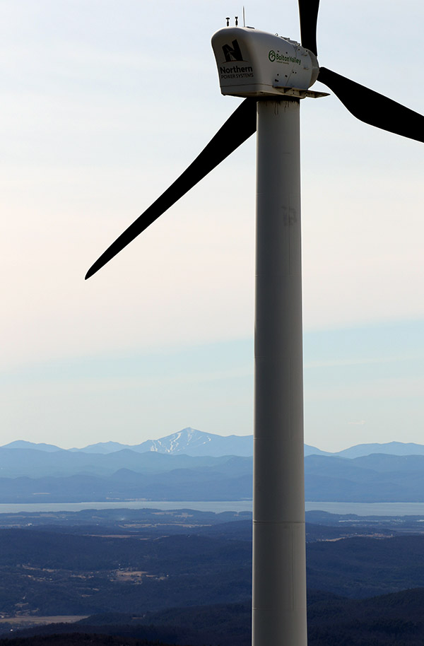 An image of the Bolton Valley wind turbine with Lake Champlain and Whiteface Mountain taken from the Vista Peak Fire Tower at Bolton Valley Resort in Vermont