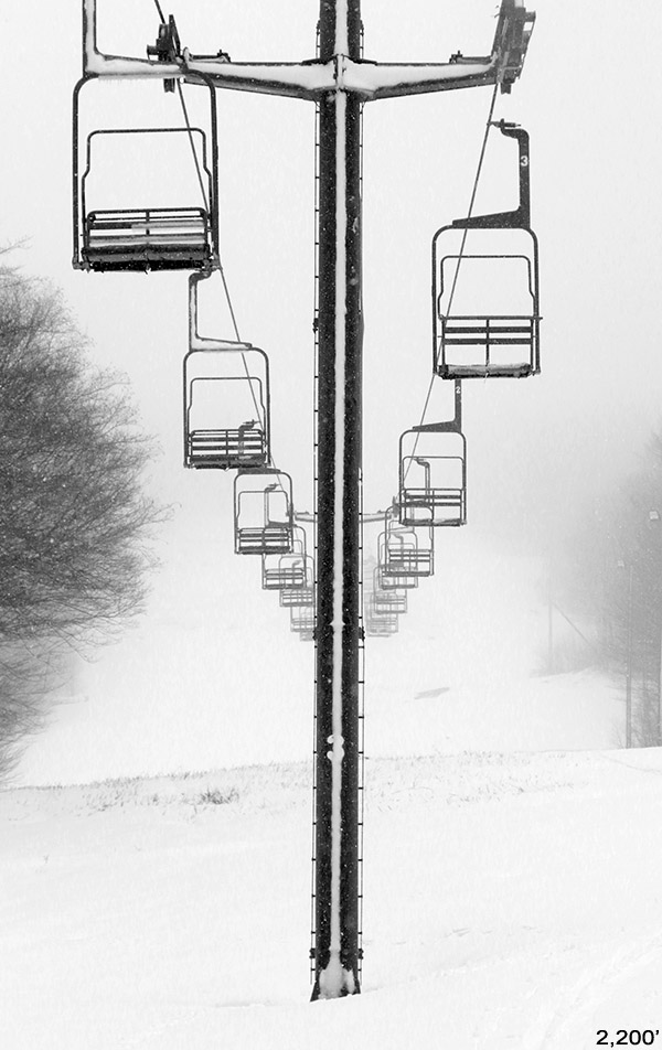 An image of the Mid Mountain Double Chairlift at Bolton Valley Ski Resort in Vermont after a late April snowfall