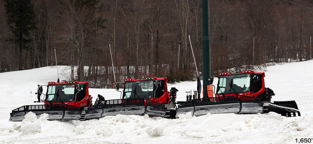An image snowing some of the snow cats from Stowe Mountain Resort in Vermont assembled above the Midway Lodge