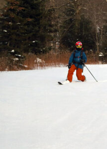 An image of Dylan Telemark skiing in some November powder on the Turnpike trail at Bolton Valley Resort in Vermont.