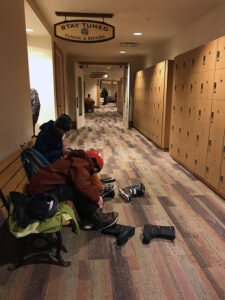An image of Ty and Dylan getting their ski gear on in the locker area of the Spruce Camp base lodge at Stowe Mountain Resort in Vermont.