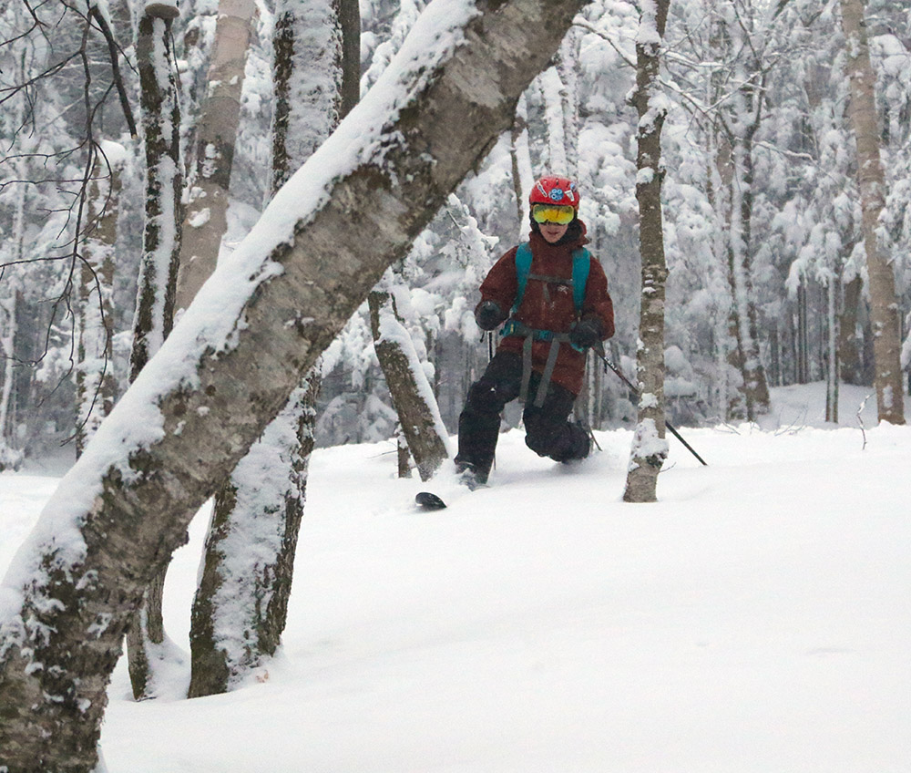 An image of Dylan Telemark skiing in powder on the backcountry network at Bolton Valley Resort in Vermont