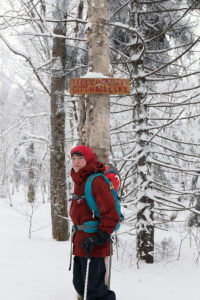 An image of Dylan below the Gotham City sign in the backcountry ski trail network at Bolton Valley Resort in Vermont