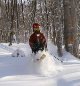 An image of Dylan skiing in powder snow at Bolton Valley Resort in Vermont after nearly two feet of snow from Winter Storm Kade