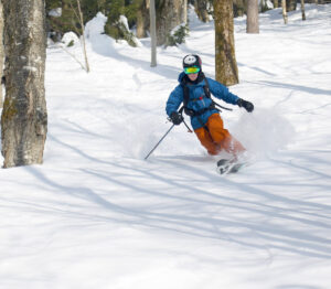 An image of Ty Telemark skiing in some powder on a sunny February day on the Backcountry Trail Network at Bolton Valley Ski Resort in Vermont
