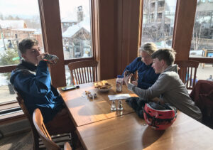 An image of Erica and the boys having a snack at the Great Room Grill in the Spruce Camp Lodge at Stowe Mountain Ski Resort in Vermont