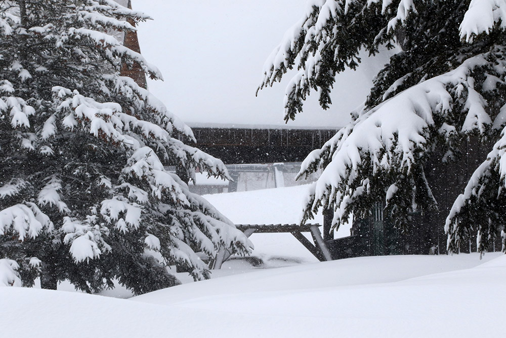 A snowy view of the Timberline Base Lodge during Winter Storm Odell at Bolton Valley Ski Resort in Vermont
