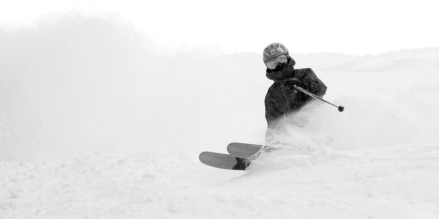 An image of Dylan tossing up a spray of powder snow from Winter Storm Odell while skiing the headwall of the Tattle Tale trail at Bolton Valley Resort in Vermont