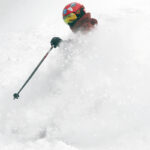 Dylan creating a wall of powder as he skis fresh snow form Winter Storm Odell at Bolton Valley Resort in Vermont