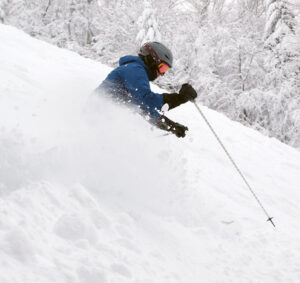 An image of Erica spraying powder snow from Winter Storm Odell as she skis at Bolton Valley Resort in Vermont