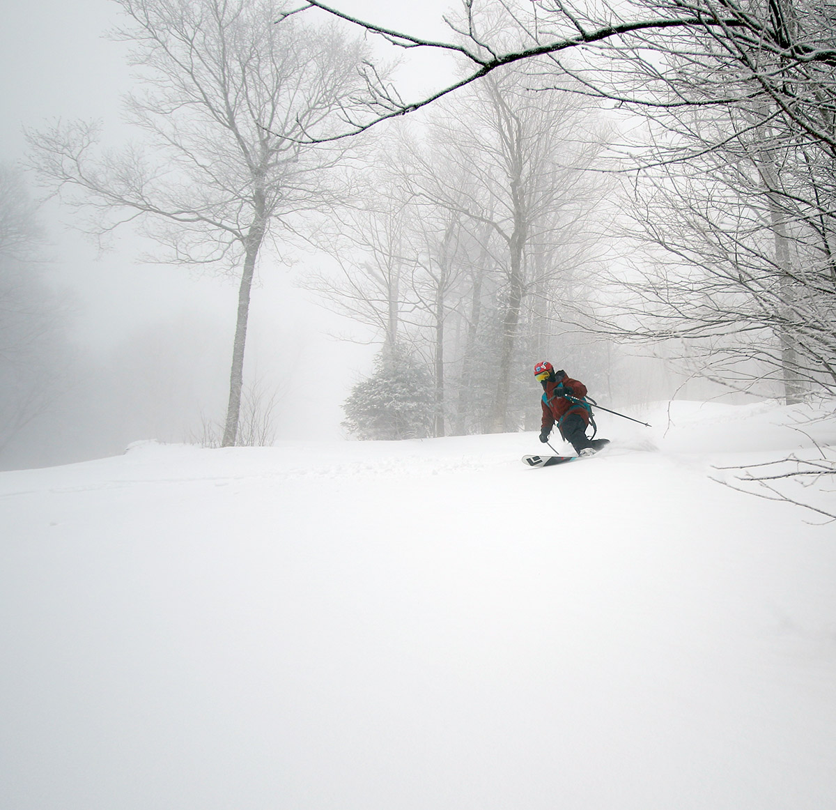 A wide-angle image of Dylan skiing in powder from Winter Storm Quincy out on a ski tour at Bolton Valley Resort in Vermont