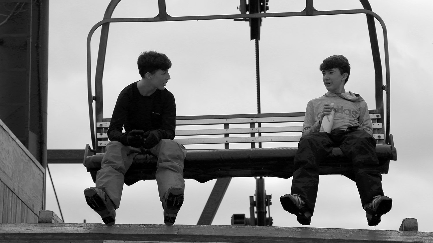 An image of Ty and Dylan on a chair of the Timberline Quad Chairlift during a ski tour at Bolton Valley Resort in Vermont.