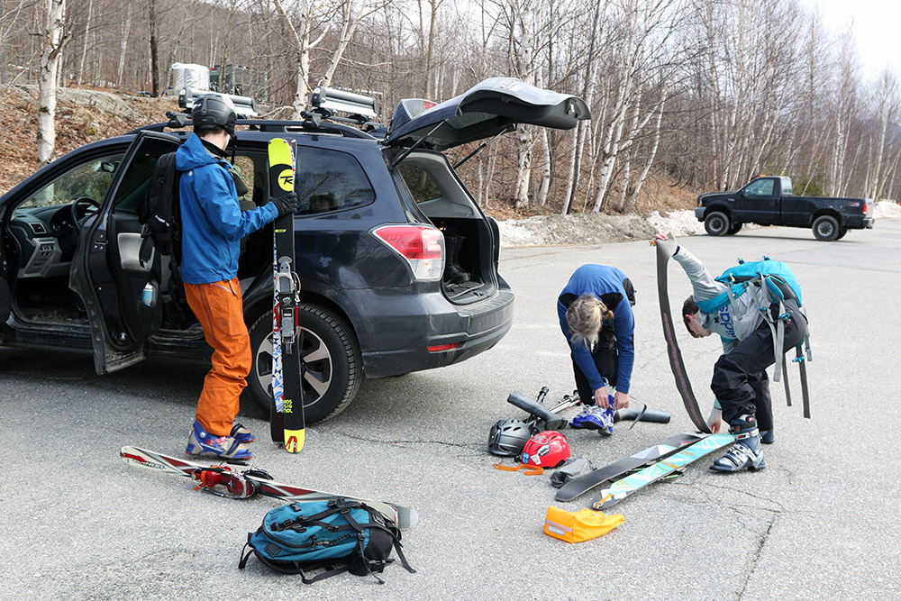 An image of Erica, Ty, and Dylan preparing their gear for a spring ski tour at Bolton Valley Resort in Vermont