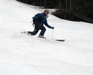 An image of Erica Telemark skiing on the Showtime trail during a spring ski tour at Bolton Valley Resort in Vermont