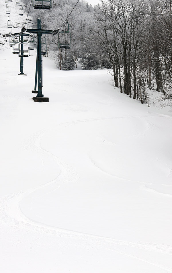 An image of ski tracks in powder snow on the Bolton Outlaw trail after an April snowstorm at Bolton Valley Ski Resort in Vermont