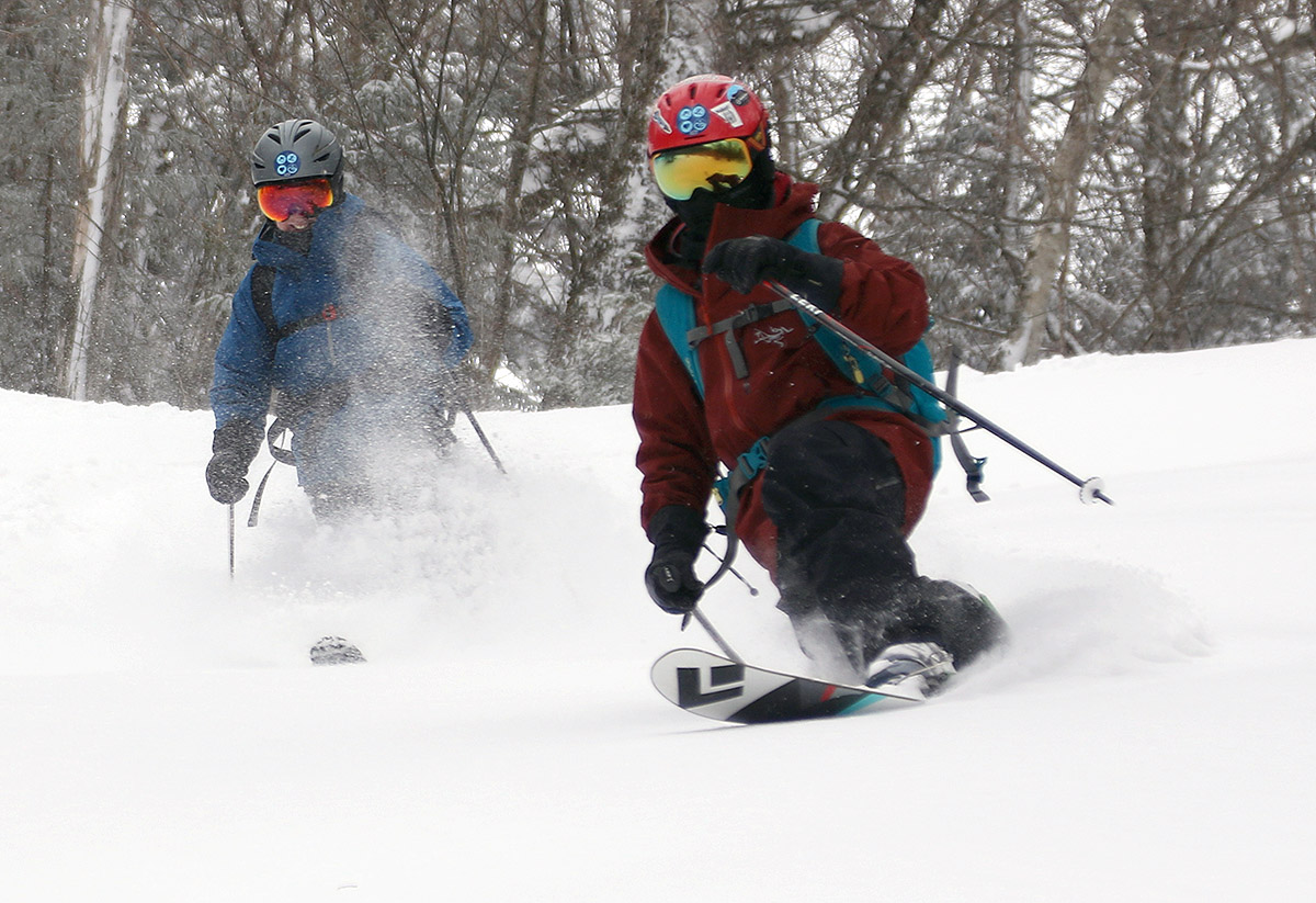 An image of Erica and Dylan skiing powder together during an April snowstorm at Bolton Valley Resort in Vermont