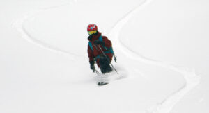 An image of Dylan Telemark skiing in powder during an April snowstorm at Bolton Valley Ski Resort in Vermont