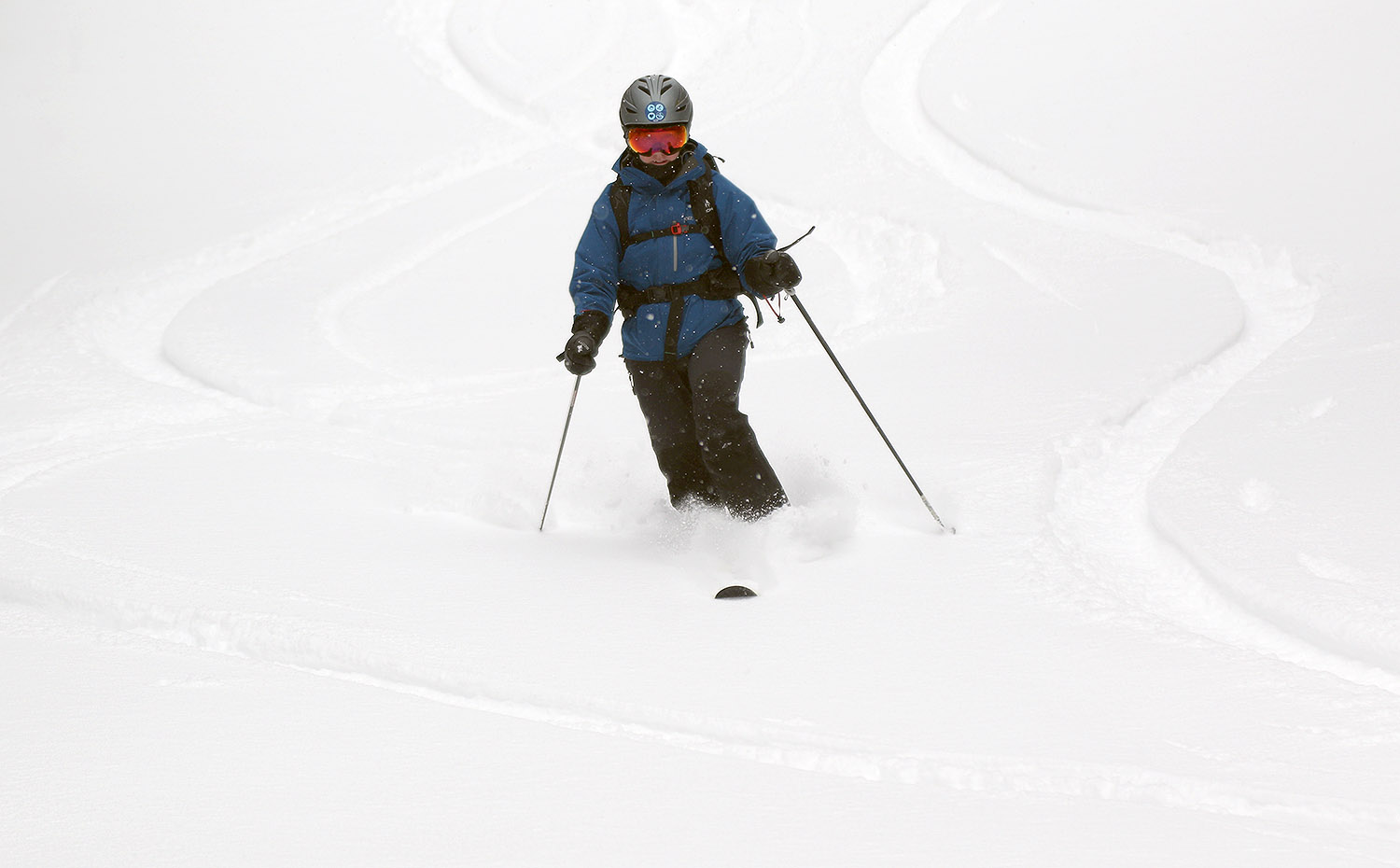 An image of Erica Telemark skiing on powder during an April snowstorm at Bolton Valley Ski Resort in Vermont