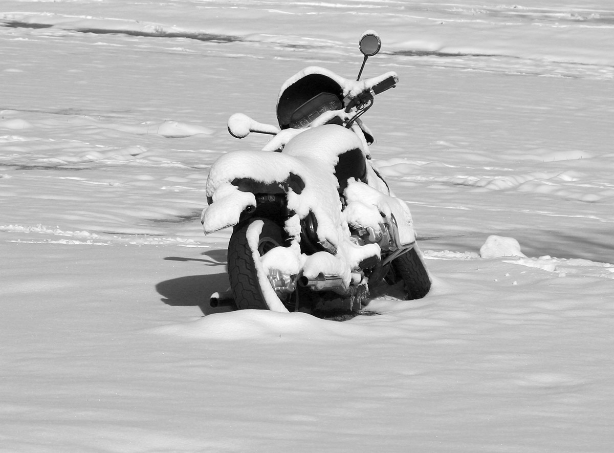 An image of a motorcycle covered in fresh snow from a mid-May snowstorm in the village parking lot at Bolton Valley Ski Resort in Vermont