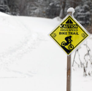 An image of a bike trail sign at Bolton Valley Resort in Vermont while out on a ski tour at the mountain during an early November snowstorm