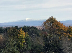 An image of Mt. Mansfield in Vermont taken from the Burlington area in late October showing some valley foliage and snow in the mountain peaks from a recent storm