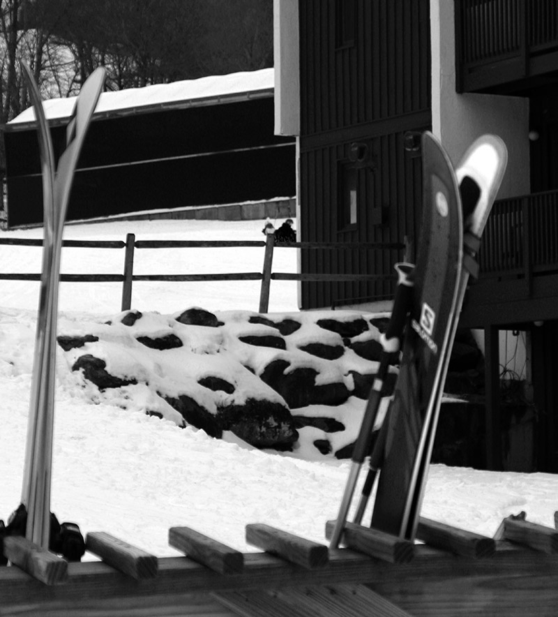 A scene with a couple pairs of skis on a ski rack and some snowy rocks in the background at the main base area at Bolton Valley Ski Resort in Vermont