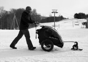 An image of someone pushing a stroller on snow with a ski on the front wheel at Bolton Valley Ski Resort in Vermont