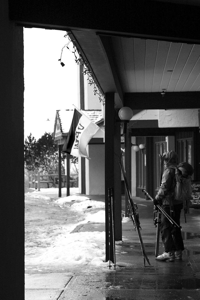 An image of Erica standing in the Bolton Valley Village circle area with some skis after a Telemark ski tour at the resort