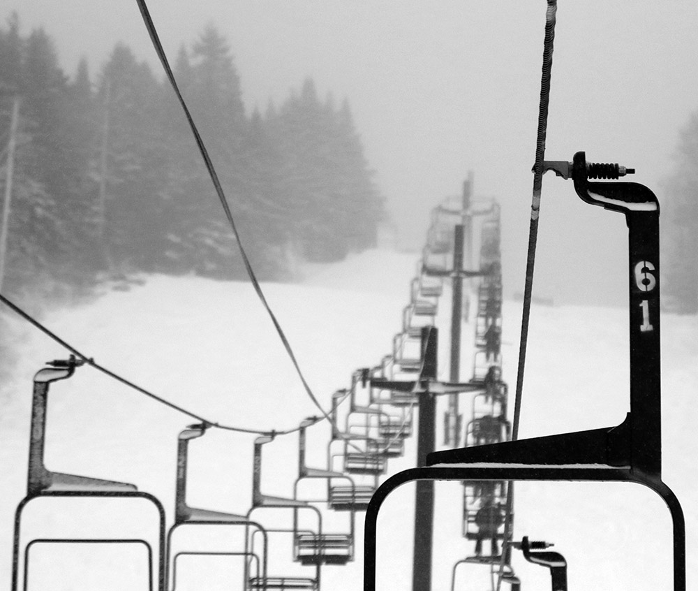 An image of the Mid Mountain Double Chair disappearing into the clouds on a snowy morning at Bolton Valley Ski Resort in Vermont