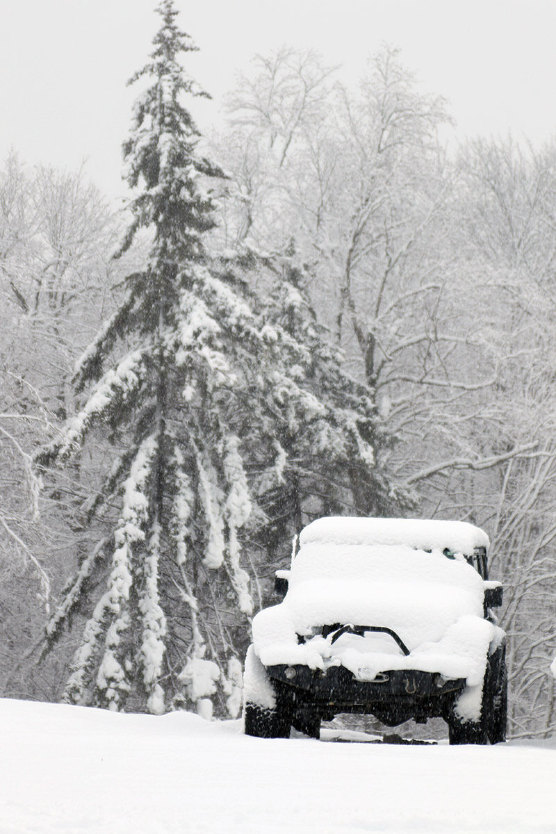 An image of a jeep with trees in the background covered with heavy wet snow from Winter Storm Malcolm at the Timberline Base Area of Bolton Valley Ski Resort in Vermont